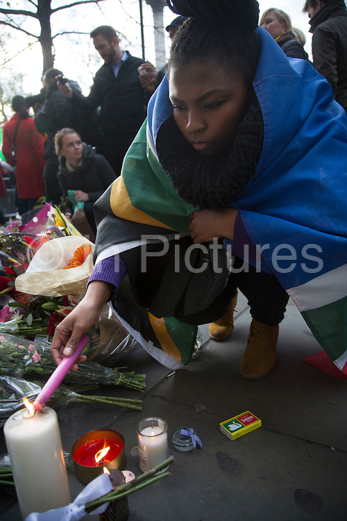 London, UK 6th December 2013: People gather near to the South African Embassy to light candles to pay tribute to former South African leader and anti-apartheid ANC campaigner Nelson Mandela, who died aged 95 on 5th December 2013.