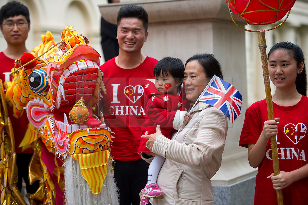 © Licensed to London News Pictures. 20/10/2015. London UK. A young Chinese girl holding a union jack flag poses for a picture with a dragon on The Mall in London leading to Buckingham palace as Chinese President Xi Jinping starts day one of a four day State Visit to the United Kingdom. Photo credit: Ben Cawthra/LNP