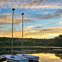 Massachusetts sunset photography from Wellesley College at Lake Waban in Wellesley Massachusetts showing a couple sailboats with surrounding beautiful evening hues. This Massachusetts lake with Wellesley College nearby are inspiring and make for a beautiful New England nature photography location to visit and to get lost with a camera.<br />