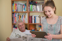 Portrait of grandfather reading newspaper and granddaughter using in digital tablet in living room, smiling