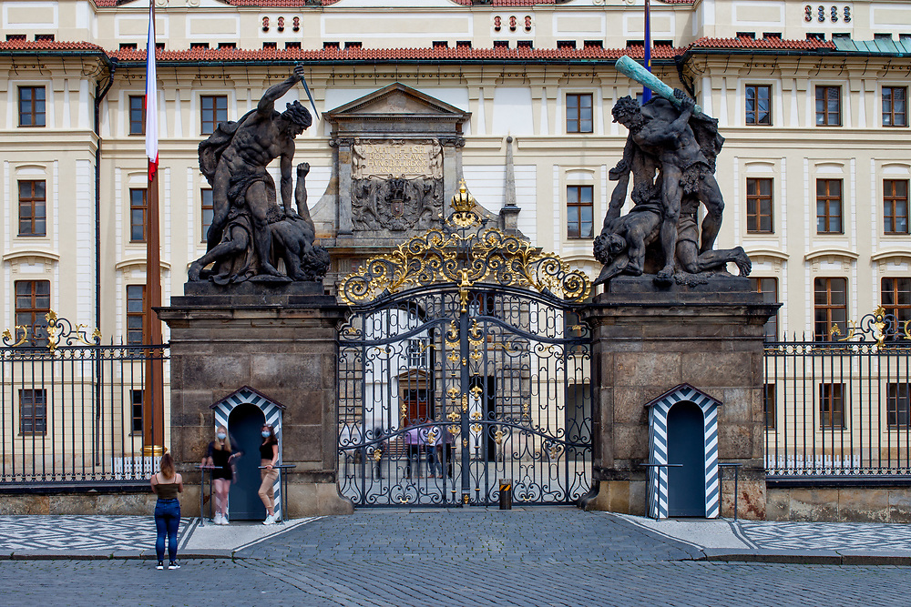 """Two young women getting a photograph while wearing face-masks in-front of the Wrestling Titans (Sousoší Souboj Titánů) at an empty Prague Castle and """"Hradcany Square"""" (Hradcanske Namesti). The Czech government lowered the scurity measures and as of Monday 25 May 2020, wearing of protective masks will be mandatory only in the interiors of buildings other than the place of residence and in public transport."""