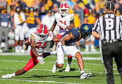 Sep 4, 2021; College Park, Maryland, USA; Maryland Terrapins defensive back Kenny Bennett (24) strips the ball from West Virginia Mountaineers wide receiver Winston Wright Jr. (1) during a punt return during the second quarter at Capital One Field at Maryland Stadium. Mandatory Credit: Ben Queen-USA TODAY Sports
