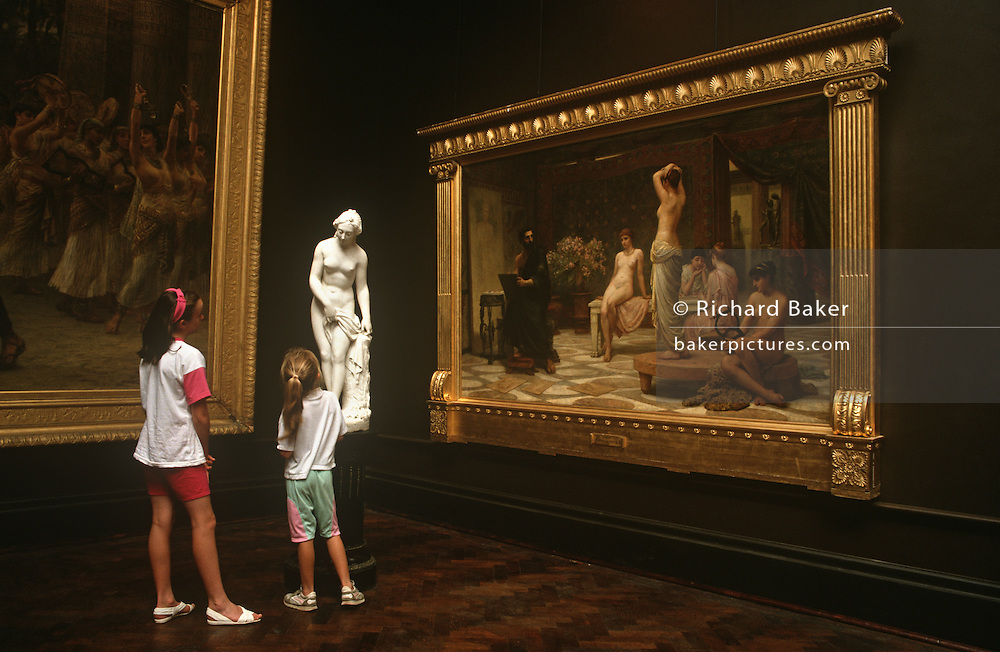Two young girls admire a statuette in front of the painting called The Chosen Five (Zeuxis At Crotona) by Edwin Longsden Long. ..Russell-Cotes Museum (formally, the Russell-Cotes Art Gallery & Museum) is an art gallery and museum in Bournemouth, England. It is located on the top of the East Cliff, next to the Royal Bath Hotel.