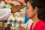 """29 SEPTEMBER 2012 - NAKORN NAYOK, THAILAND:   Brahman priests anoint Thai Buddhists during observances of Ganesh Ustav at Wat Utthayan Ganesh, a temple dedicated to Ganesh in Nakorn Nayok, about three hours from Bangkok. Many Thai Buddhists incorporate Hindu elements, including worship of Ganesh into their spiritual life. Ganesha Chaturthi also known as Vinayaka Chaturthi, is the Hindu festival celebrated on the day of the re-birth of Lord Ganesha, the son of Shiva and Parvati. The festival, also known as Ganeshotsav (""""festival of Ganesha"""") is observed in the Hindu calendar month of Bhaadrapada, starting on the the fourth day of the waxing moon. The festival lasts for 10 days, ending on the fourteenth day of the waxing moon. Outside India, it is celebrated widely in Nepal and by Hindus in the United States, Canada, Mauritius, Singapore, Thailand, Cambodia, Burma , Fiji and Trinidad & Tobago.    PHOTO BY JACK KURTZ"""