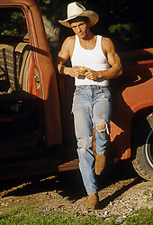 cowboy leaning against an old pick up truck outdoors