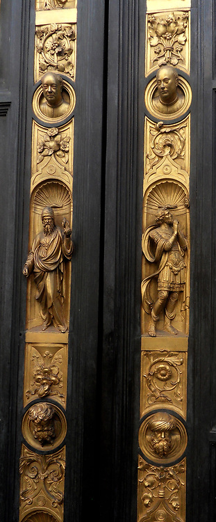 Detail from the Battistero di San Giovanni (Florence Baptistery). The baptistery Considered a minor basilica, and is a religious building in Florence, Italy. It is in the Florentine Romanesque style, and was built between 1059 and 1128, making it one of the oldest buildings in the city. 3 sets of bronze doors with relief sculptures are on the exterior. The south doors created by Andrea Pisano, and the east and north doors by Lorenzo Ghiberti. Here we see some of the embellishments around the main panels, including portraits of the artist, saints and religious images.