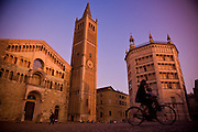 A bicyclist zooms by a Cathedral in an open square in Italy