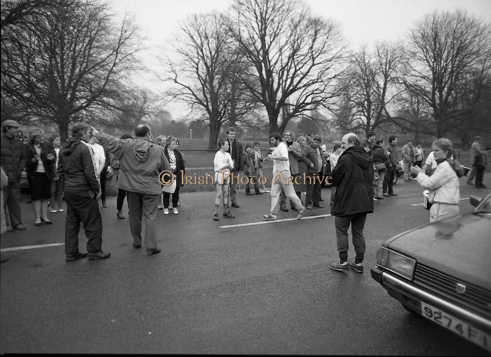 First All-Traveller Mini Marathon.    (R53)..1987..05.04.1987..04.05.1987..5th April 1987..Today saw the running of the first All-Traveller Mini Marathon in aid of Trocaire the World Aid Agency. The race was run over a 10k course in the Phoenix Park, Dublin. Bishop Eamon Casey a patron of the charity was on hand to lend support...Image shows some stragglers getting encouragement from the crowd along the road.