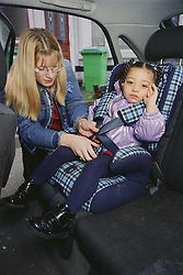 Young mother fastening daughter into child car seat,