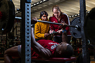 Luvna Dhawka  '20, stands with Krista Ingram, Associate Professor of Biology as they observe Abu Daramy '20 bench pressing in Huntington Gymnasium November 14, 2019.