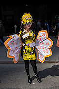 """New York, NY, USA-27 March 2016. A woman wearing a bee costume with two signs on it: """"Bee"""" and  """"Happy"""" in the annual Easter Bonnet Parade and Festival."""