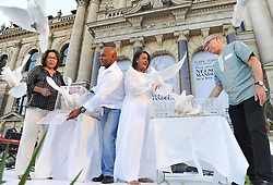 The Executive Mayor of Cape Town, PATRICIA DE LILLE, former springbok rugby player, CHESTER WILLIAMS, singer VICKY SAMPSON and Minister in the Presidency, TREVOR MANUEL, release doves in remembrance of Nelson Mandela.The City of Cape Town hosted an interfaith service on the Grand Parade as the day was declared a national day of prayer and reflection on the life of Nelson Mandela. Visitors also placed flowers and condolence messages on the barricade erected to accommodate it. Various religious leaders said prayers for the late South African President, Cape Town, South Africa, Sunday, 8th December 2013. Picture by Roger Sedres / i-Images