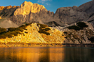 Mountain peaks colored with sunset light aove a lake