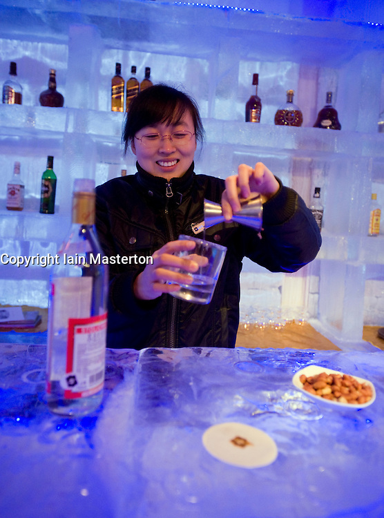 Female bartender pours a drink in the Ice Bar in Harbin China 2009