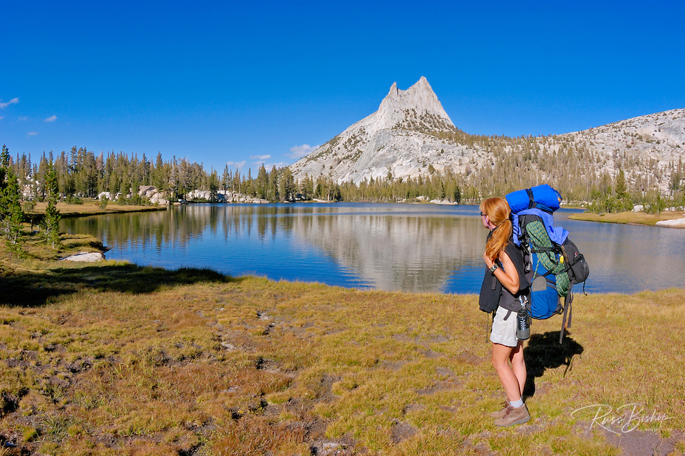 Backpacker on the shore of upper Cathedral Lake under Cathedral Peak, Yosemite National Park, California