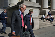 An older businessman walks with another wearing a flat cap below the classical architecture of Royal Exchange and the WW1 war memorial at Bank Triangle, on 10th May 2017, in the City of London, England.