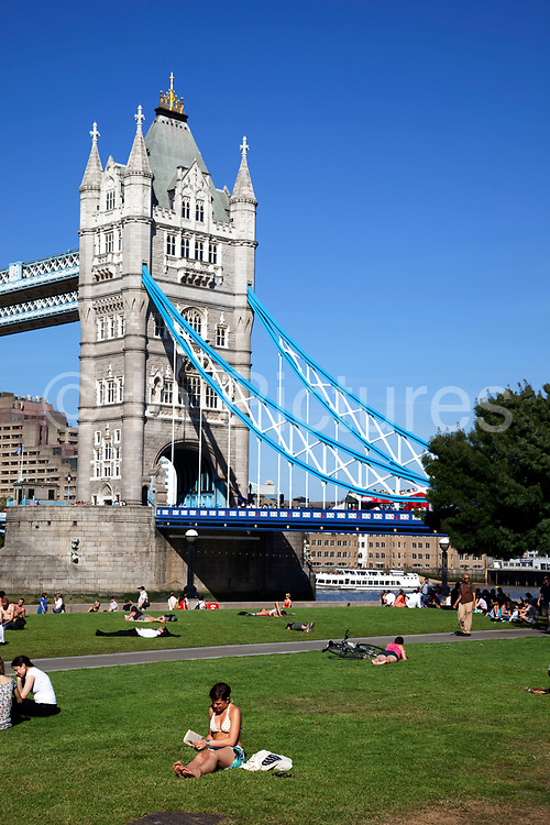 Scenes of both tourists and local office workers sunbathing on the grass at the London Bridge City Park near to Tower Bridge. This area is an icon for tourism, bringing thousands in each day.