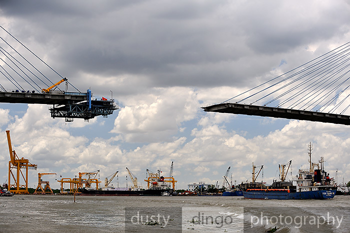 Sections of the Phu My bridge, a 705m long cable-stayed crossing with a central span of 380m, inch together high above the Saigon River. Ho Chi Minh City (Saigon), Vietnam