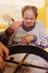 Man with learning difficulties playing musical instrument during music workshop,