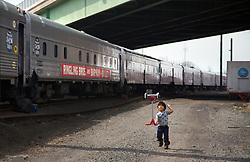 """Kauile dos Santos, 7, the son of Brazilian actor Paulo Cesar Oliveira dos Santos practices his moves near the parked train. He hopes to be just like his father someday.<br /> <br /> Ringling Bros. and Barnum & Bailey Circus started in 1919 when the circus created by James Anthony Bailey and P. T. Barnum merged with the Ringling Brothers Circus. Currently, the circus maintains two circus train-based shows, the Blue Tour and the Red Tour, as well as the truck-based Gold Tour. Each train is a mile long with roughly 60 cars: 40 passenger cars and 20 freight. Each train presents a different """"edition"""" of the show, using a numbering scheme that dates back to circus origins in 1871 — the first year of P.T. Barnum's show."""