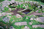 Prehistoric buildings at Drombeg henge site, County Cork, Ireland.  The stone trough of water is thought to have been associated with cooking suggesting that this building was a kitchen of some sort