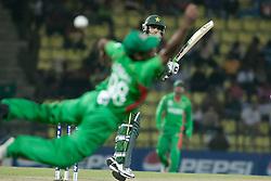 © Licensed to London News Pictures. 25/09/2012. Pakistan batsmen Mohammad Hafeez edges one past a diving Bangladesh fielder during the T20 Cricket World T20 match between Pakistan Vs Bangladesh at the Pallekele International Stadium Cricket Stadium, Pallekele. Photo credit : Asanka Brendon Ratnayake/LNP