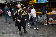 "Town Crier Alan Myatt calling out his announcements and ringing his hand bell in Stables Market area of Camden Market, Camden Town, London, UK. A town crier, or bellman, is an officer of the court who makes public pronouncements as required by the court. The crier can also be used to make public announcements in the streets. Criers often dress elaborately, by a tradition dating to the 18th century, in a red and gold robe, white breeches, black boots and a tricorne hat. They carry a handbell to attract people's attention, as they shout the words ""Oyez, Oyez, Oyez!"" before making their announcements. The word ""Oyez"" means ""hear ye,"" which is a call for silence and attention."
