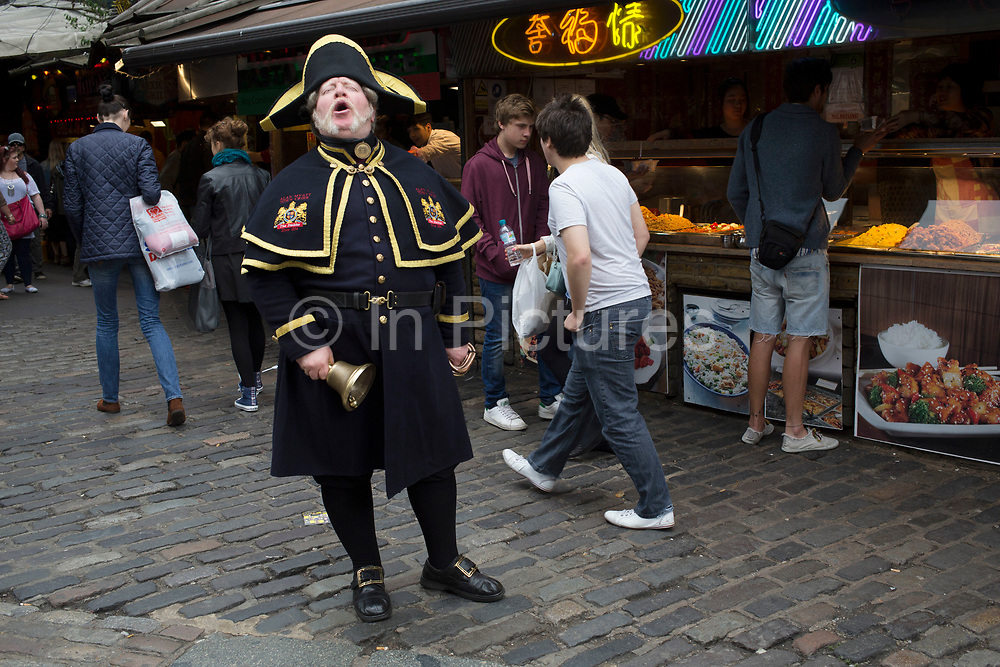 """Town Crier Alan Myatt calling out his announcements and ringing his hand bell in Stables Market area of Camden Market, Camden Town, London, UK. A town crier, or bellman, is an officer of the court who makes public pronouncements as required by the court. The crier can also be used to make public announcements in the streets. Criers often dress elaborately, by a tradition dating to the 18th century, in a red and gold robe, white breeches, black boots and a tricorne hat. They carry a handbell to attract people's attention, as they shout the words """"Oyez, Oyez, Oyez!"""" before making their announcements. The word """"Oyez"""" means """"hear ye,"""" which is a call for silence and attention."""