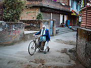 04 MARCH 2017 - KATHMANDU, NEPAL: A man pushes his bicycle through a residential neighborhood in Kathmandu.    PHOTO BY JACK KURTZ