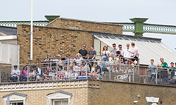Spectators on a roof top over looking the Oval wach the game