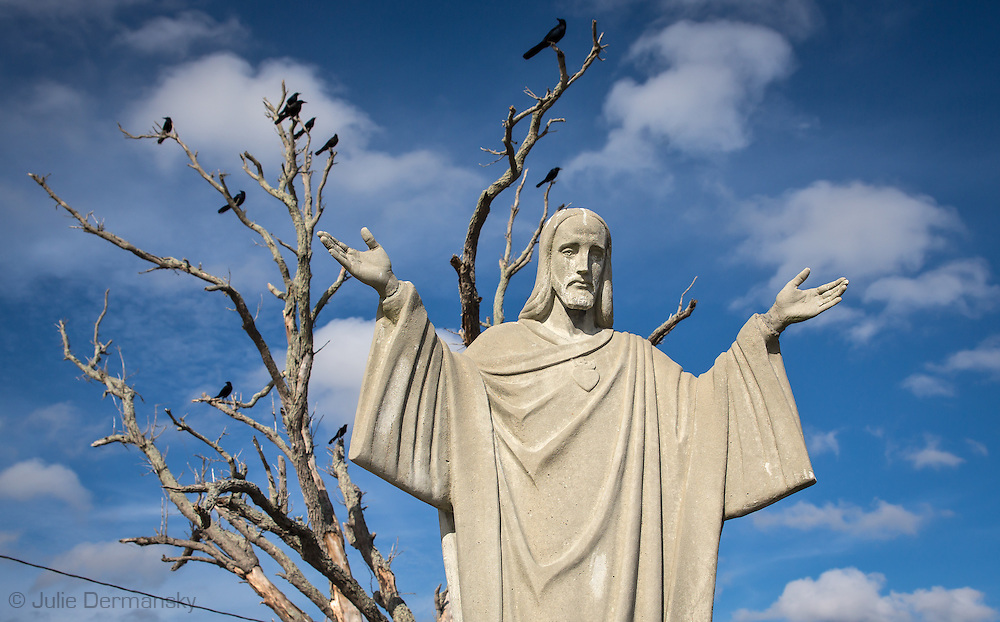 Crows on a tree in the parking lot of the Pointe-aux-Chenes marina behind a sculture of Christ.