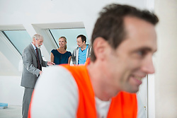 Architect, couple and construction worker at construction site of new building
