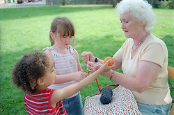 Grandmother teaching granddaughter how to knit,