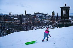 Edinburgh, Scotland, UK. 21 January 2020. Storm Christoph brought overnight snow to Edinburgh. Pic; Sisters Iris and Rosalie from Edinburgh enjoy sledging on Calton Hill in front of famous skyline view. Iain Masterton/Alamy Live News