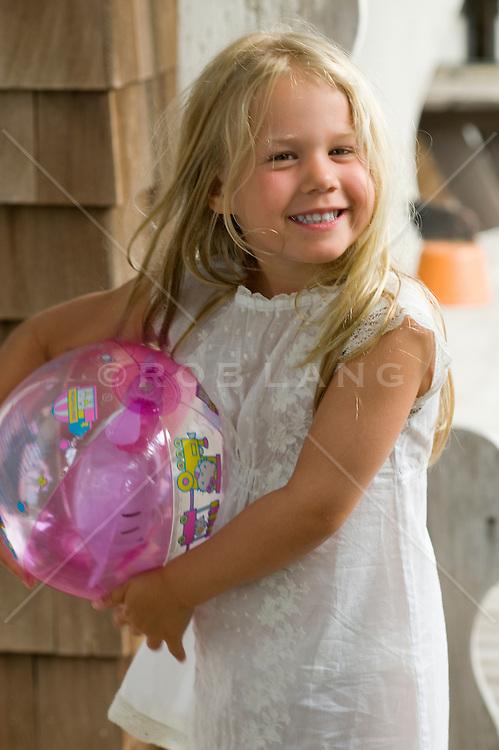 cute little girl holding a ball outdoors