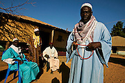 "Men chat and wait around the house of the holy man in Bafata-Oio village, Aladji Fode Mai Toure, expecting his blessing and listening to his advice. Locally known as ""Homem Grande"", meaning 'great man', serving as a community and local leader. Half of the population are considered to be muslim."