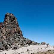 A porter walks past the base of Lava Tower against a clear blue sky on Mt Kilimanjaro's Lemosho Route.