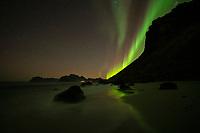Northern Lights - Aurora Borealis shine in night sky over Myrland beach, Flakstadøy, Lofoten Islands, Norway