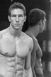 portrait of a shirtless muscular man against a mirror