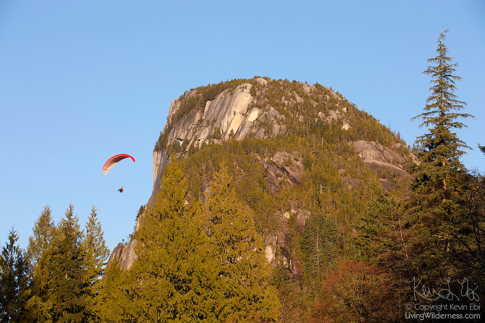 A paraglider flies from the summit of Stawamus Chief, a 702 meter (2,303 foot) granite dome near Squamish, British Columbia, Canada. Geologists believe Stawamus Chief is a remnant of a magma chamber that was once well below the Earth's surface. Slow moving molten magma cooled and turned into granite deep below the surface and was gradually exposed by erosion over tens of millions of years. The peak is popular with rock climbers and paragliders.