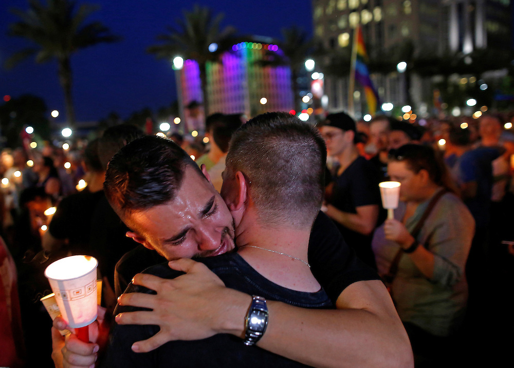 People embrace during a candlelight vigil at a memorial service for the victims of the shooting at the Pulse gay nightclub in Orlando, Florida, June 13, 2016. REUTERS/Jim Young