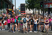 Summertime in London, England, UK. Crowds of tourists and shoppers gather in Leicester Square. This remains one of London's tourism hot spots with entertainers and shop and space to hang out. There are a huge number of student tour groups which move around en masse.