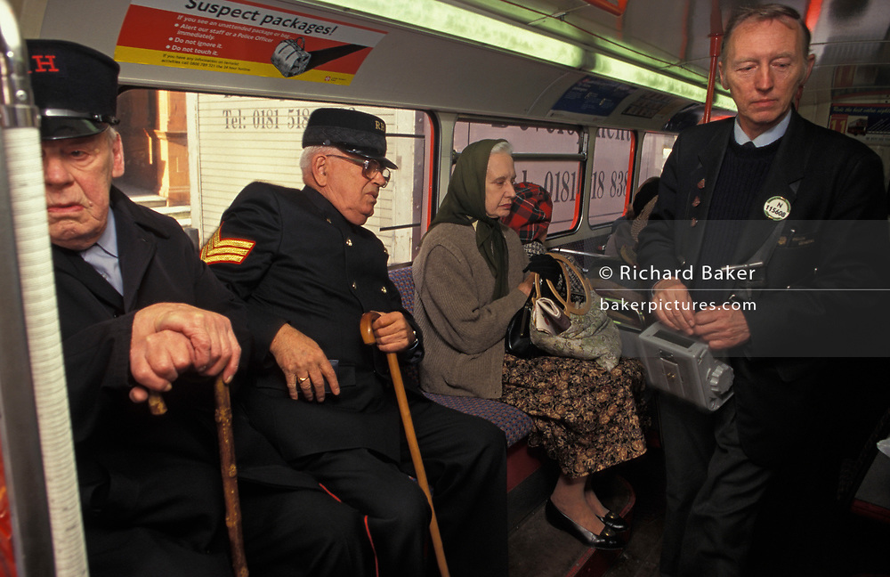 As a bus conductor asks for their fares, a Chelsea Pensioner reaches for change alongside another veteran soldier and an elderly lady, on a Routemaster bus, on 22nd November 1997, in London, England.