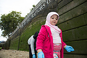 Families looking for artifacts on the river shoreline at low tide on Tower Beach, this group of Muslim girls searches aroud the entrance to Traitors Gate. This part of the Thames beach is only open once or twice a year. Totally Thames takes place over the whole month in September, combining arts, cultural and river events presented by Thames Festival Trust throughout the 42-mile stretch of the River Thames in London, UK.