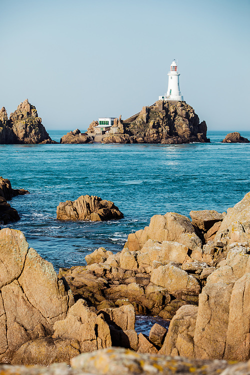 Corbiere lighthouse, the tourist attraction on the west coast of Jersey, surrounded by calm blue sea at high tide in Jersey, Channel Islands