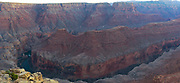 On the edge of the Grand Canyon at Tatahatso Point, with the Vermilion Cliffs in the background.