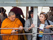 15 OCTOBER 2014 - BANGKOK, THAILAND:  A Chinese tourist (right) standing next to a Buddhist monk on a Chao Phraya Express Boat on the Chao Phraya River in Bangkok. The number of tourists arriving in Thailand in July fell 10.9 per cent from a year earlier, according to data from the Department of Tourism. The drop in arrivals is being blamed on continued uncertainty about Thailand's political situation. The tourist sector accounts for about 10 per cent of the Thai economy and suffered its biggest drop in visitors in June - the first full month after the army took power on May 22. Arrivals for the year to date are down 10.7% over the same period last year.   PHOTO BY JACK KURTZ
