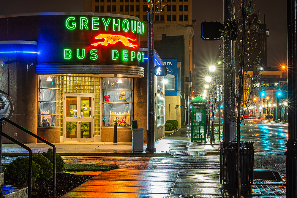 The neon lights of the bus depot in downtown Huntington cast their glow on the wet sidewalks.