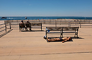 Brooklyn, NY - 14 June 2020. A man suns himself on the Coney Island boardwalk, his mask and gloves hanging from a bench, while two other people sit on a bench some distance away.