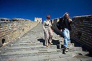 Western tourists walk the ancient Great Wall of China at Mutianyu, north of Beijing, China